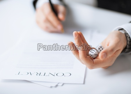 man hands with gambling dices signing