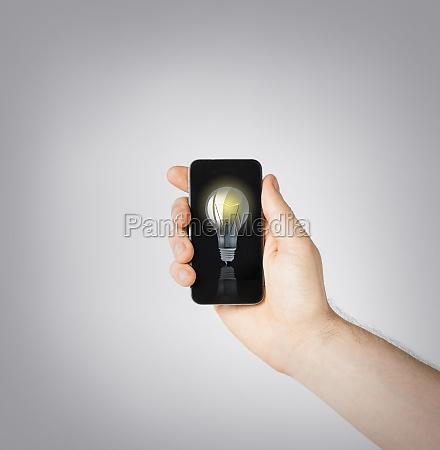 mann hand halten smartphone mit gluehbirne