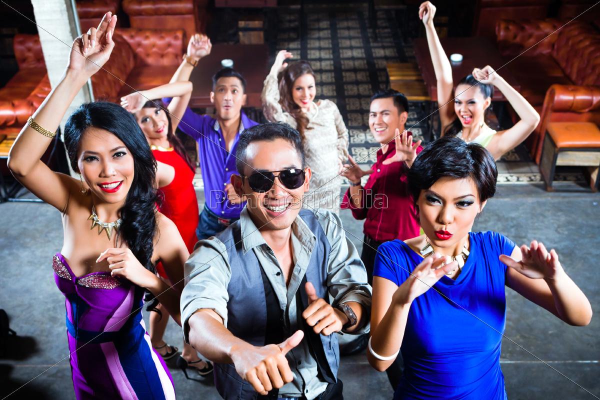 asiatische leute auf tanzfläche in diskothek feiern - lizenzfreies