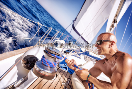 handsome strong man working on sailboat