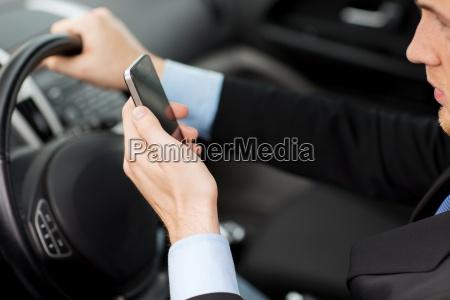 mann mit telefon waehrend der fahrt