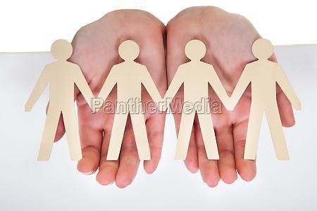 male hand holding human figure cutout