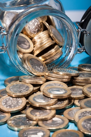 euro coins spilling from jar