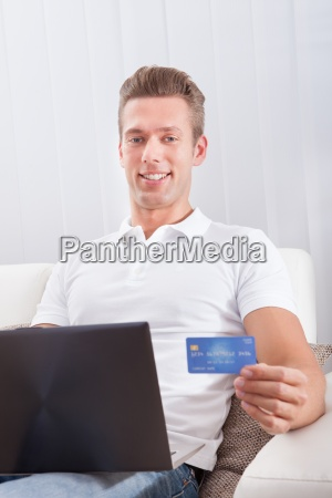 man sitting with laptop and credit