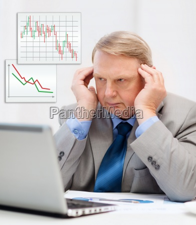 upset older businessman with laptop in