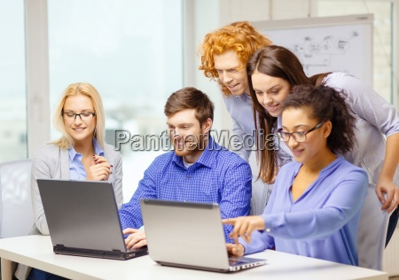 smiling team with laptop computers in