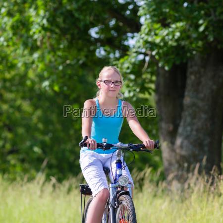 kind faehrt mit fahrrad auf feldweg