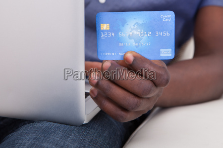hand with laptop and credit card