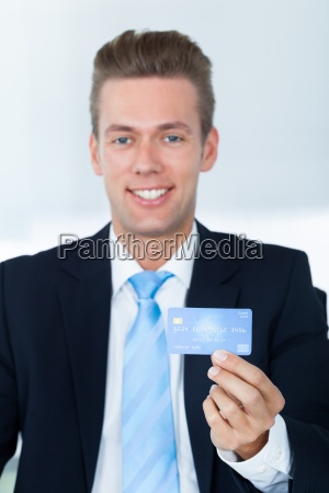 portrait of young happy businessman holding