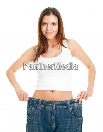 slim woman pulling oversized jeans