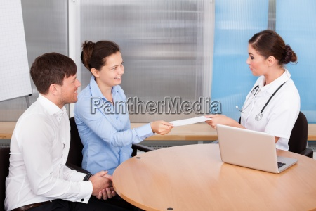doctor and woman holding envelope