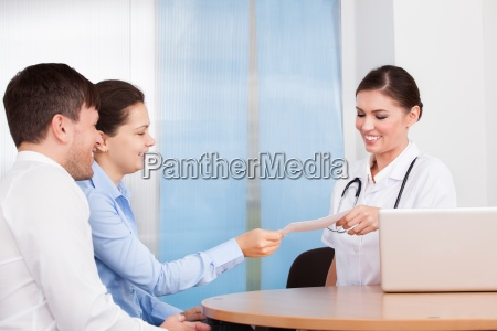 female doctor and woman holding envelope