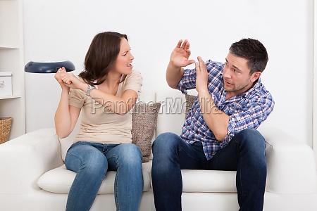 woman hitting man with sauce pan