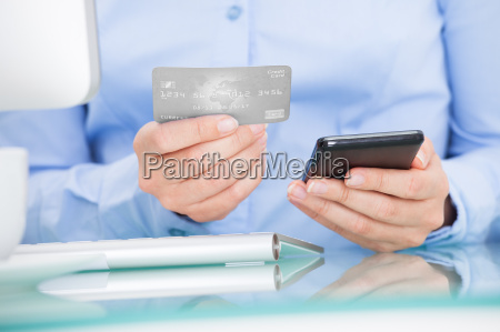 businesswoman holding cellphone and credit card
