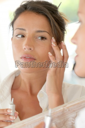 portrait of beautiful woman applying anti