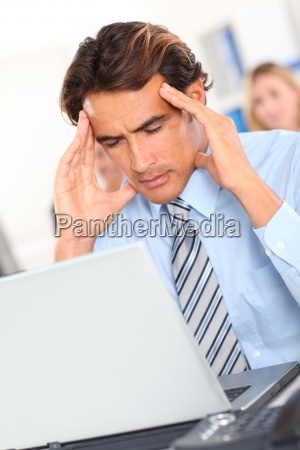 businessman having a headache in front