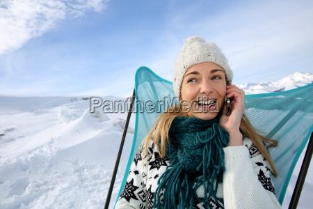 woman in ski resort using smartphone