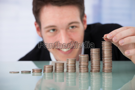 happy businessman stacking coins in increasing