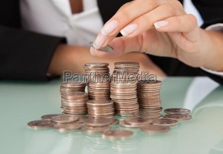 businesswomans hand stacking coins at desk