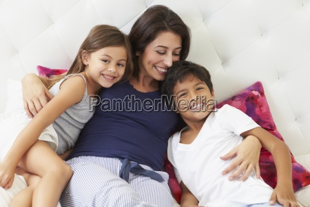 mother and children relaxing in bed