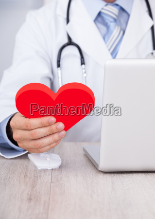 doctor holding red heart while using