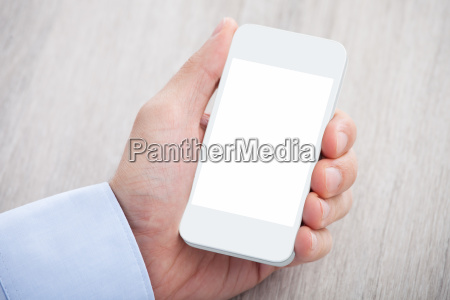 businessmans hand holding cellphone with blank