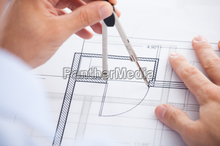 male architect using divider on blueprint