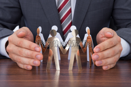 businessman protecting team of paper people