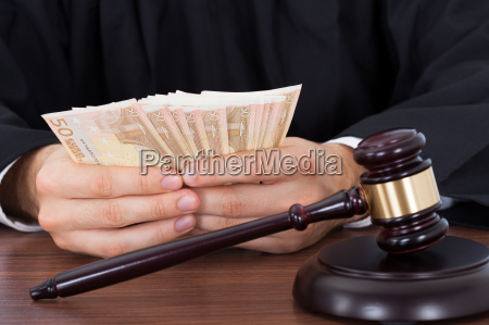 judge counting money at desk