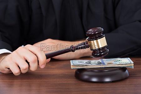 judge striking gavel on banknotes at