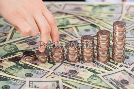 fingers walking up coinstack on dollar