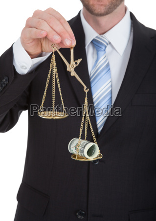 midsection of businessman weighing rolled bills