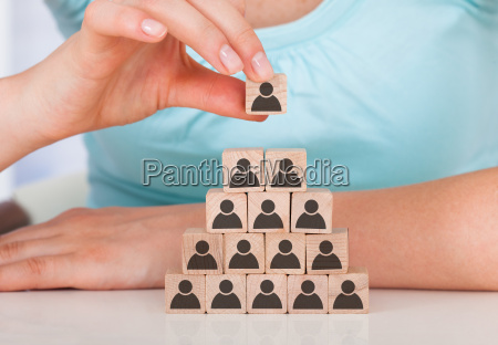 woman stacking wooden team blocks at