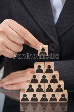 businesswoman stacking wooden team blocks