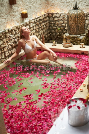 woman relaxing in flower petal covered