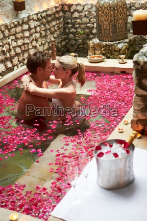 couple relaxing in flower petal covered