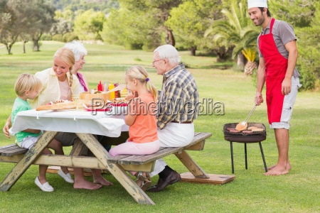 multi generation family having a barbeque