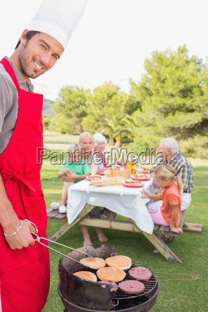 smiling father cooking a barbeque with