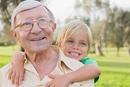 smiling grandfather giving grandson a piggy