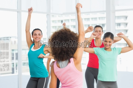 cheerful fitness class and instructor doing