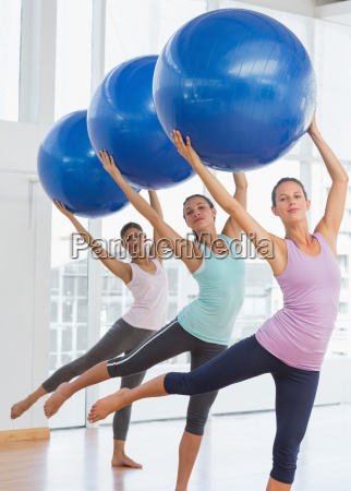 fitness class doing pilates exercise with