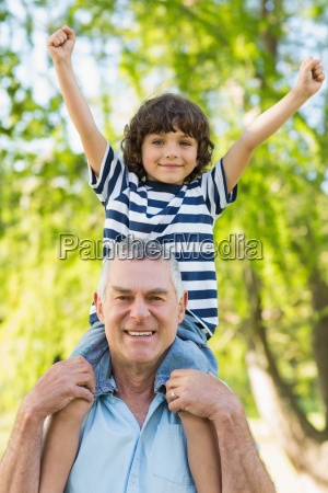 grandfather carrying son on shoulders at