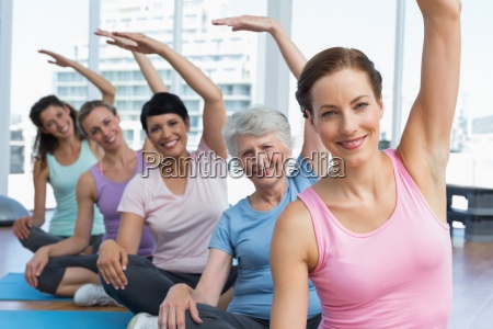 trainer with women in row stretching