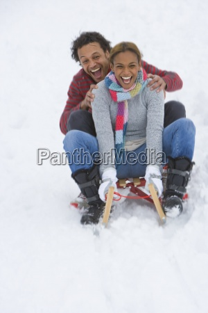 happy mixed race couple sledding down