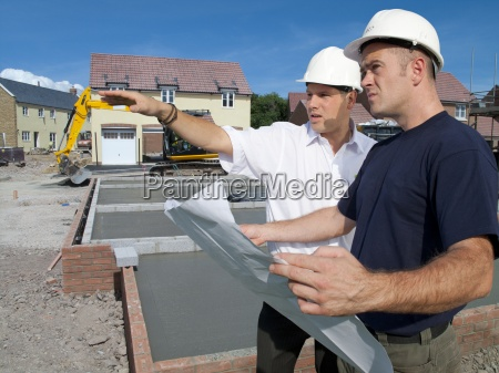 construction workers holding blueprints talking on