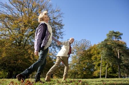 happy senior man walking and holding