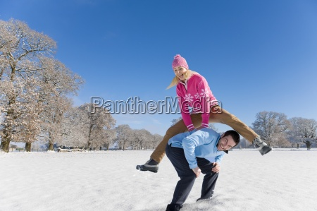 woman jumping over mans back in