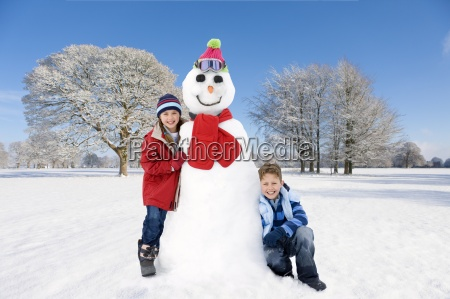 boy and girl with snowman in