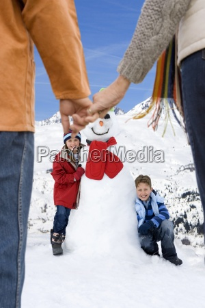 grandparents holding hands and watching children