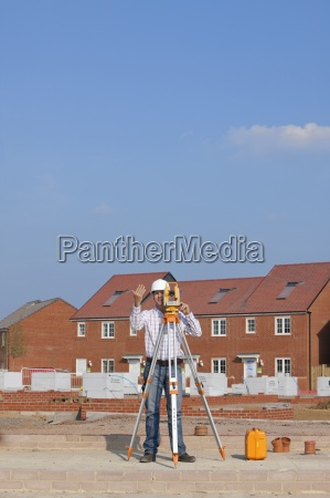 surveyor gesturing behind theodolite at construction